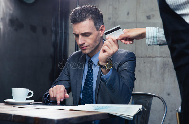 Man paying with credit card at the restaurant. Confident men paying with credit card at the restaurant stock image