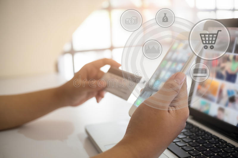 Man paying with credit card on smart phone at home office. stock image