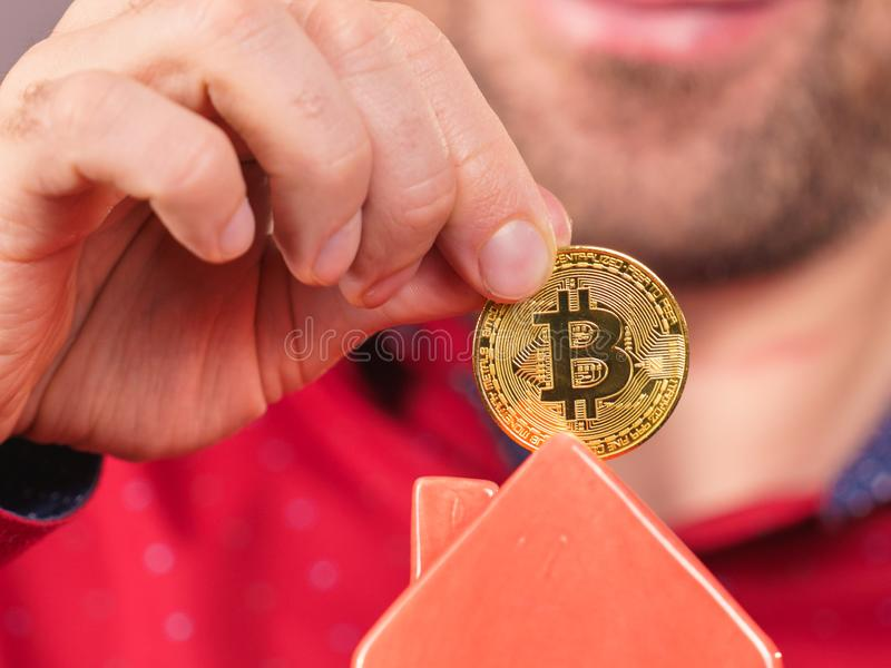 Man paying his house rent using bitcoin stock photography
