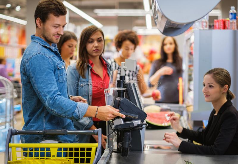 Man paying with NFC in a grocery store royalty free stock photography
