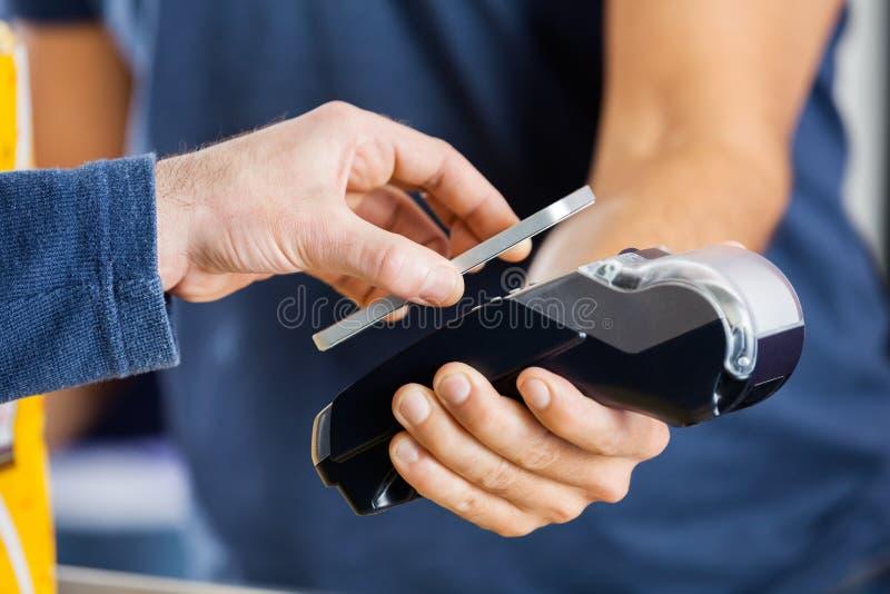Man Paying Through NFC Technology At Cinema. Cropped image of men paying through smartphone using NFC technology at cinema royalty free stock photos