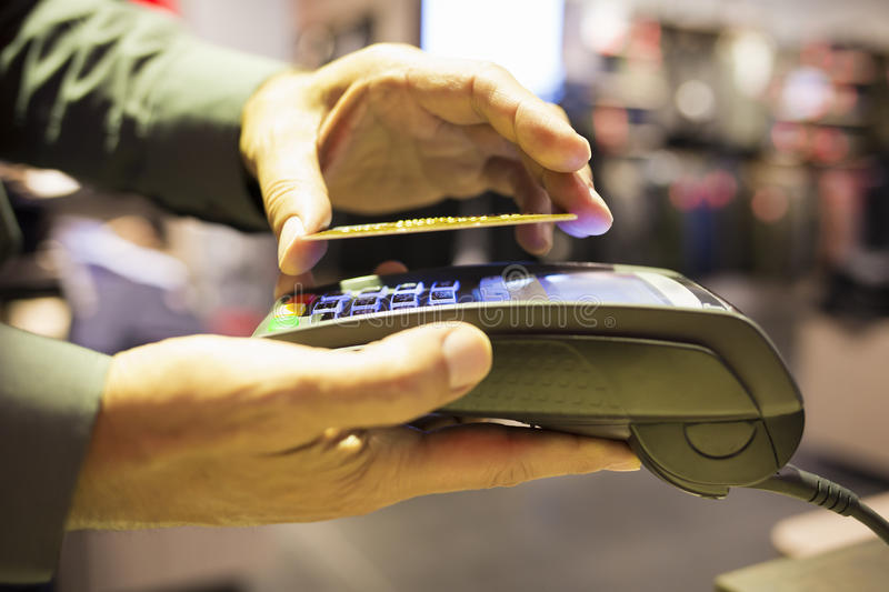 Man paying with NFC technology on credit card, in clothing store. Male Close-up electronic payment hand cell phone market stock photography