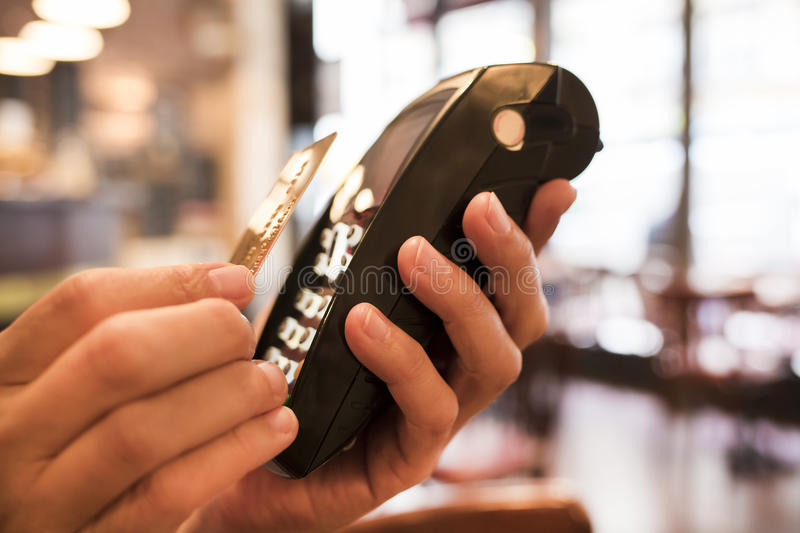Man paying with NFC technology on credit card, in restaurant, ba. Male Close-up electronic payment hand cell phone stock photography