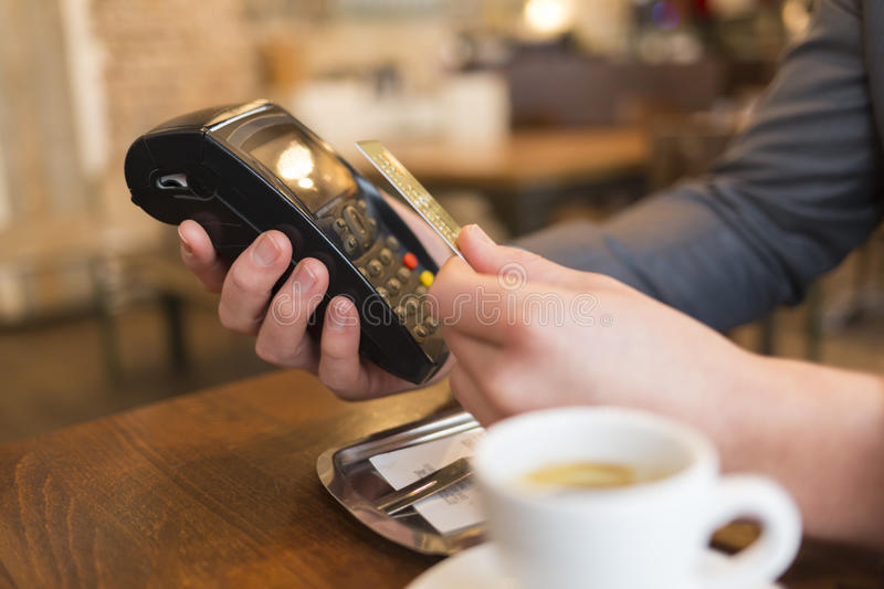 Man paying with NFC technology , credit card, in restaurant, bar. Males hands paying a bill with contact-less card in a cafe stock photos