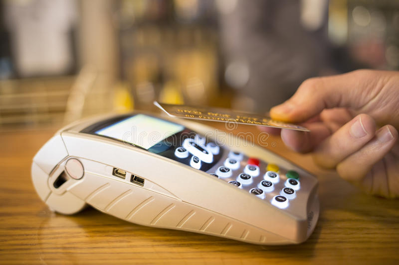 Man paying with NFC technology on credit card, restaurant, shop royalty free stock images