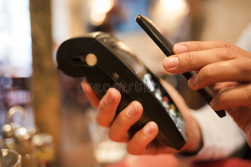 Man paying with NFC technology on mobile phone, in restaurant, b. Male Close-up electronic payment hand cell phone market stock photo