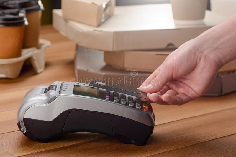 Man paying for pizza. And coffee. Contactless payment by card via POS terminal royalty free stock photos