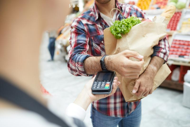 Man Paying by Smartwatch in Supermarket. Close up of unrecognizable men paying via smartwatch while grocery shopping at farmers market, copy space stock photos