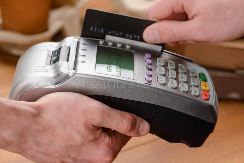 Man paying by card. Man paying with a swipe of card, close-up shot. Easy and secure cashless payment for small businesses stock photos