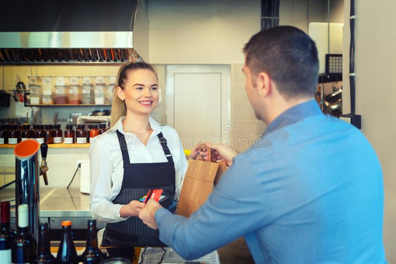 Man paying takeaway order by credit card on reader holded by smiling waitress working at shop counter restaurant. royalty free stock photos