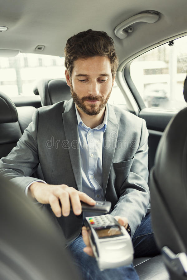 Man paying the taxi with the mobile phone. NFC technology. Man using his smartphone to pay a cab royalty free stock image