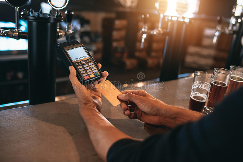 Man paying using a credit card at bar. Cropped image of man paying using a credit card at bar. Man at brewery factory with varieties of beers on counter royalty free stock photography