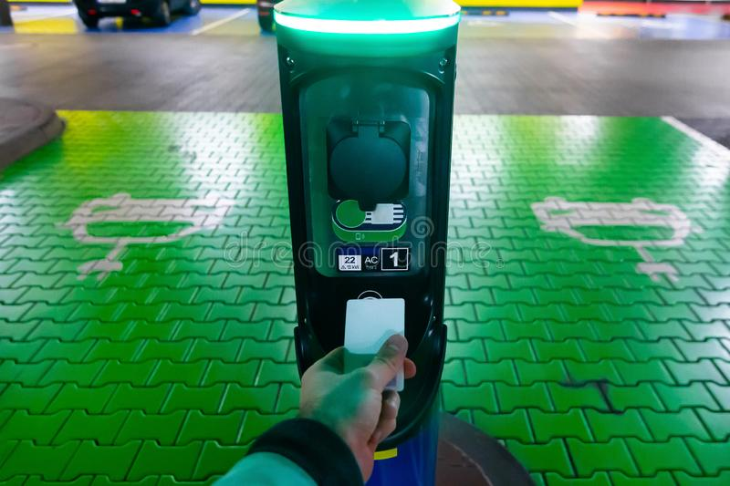 A man pays for charging an electric car. Hand holding catd to pay at charging station. Concept of green electricity, clean stock image