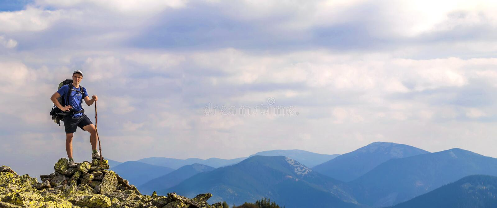 Man on peak of mountain. Emotional scene. Young man with backpack standing with raised hands on top of a mountain and enjoying mo. Untain view. Hiker on the royalty free stock photo