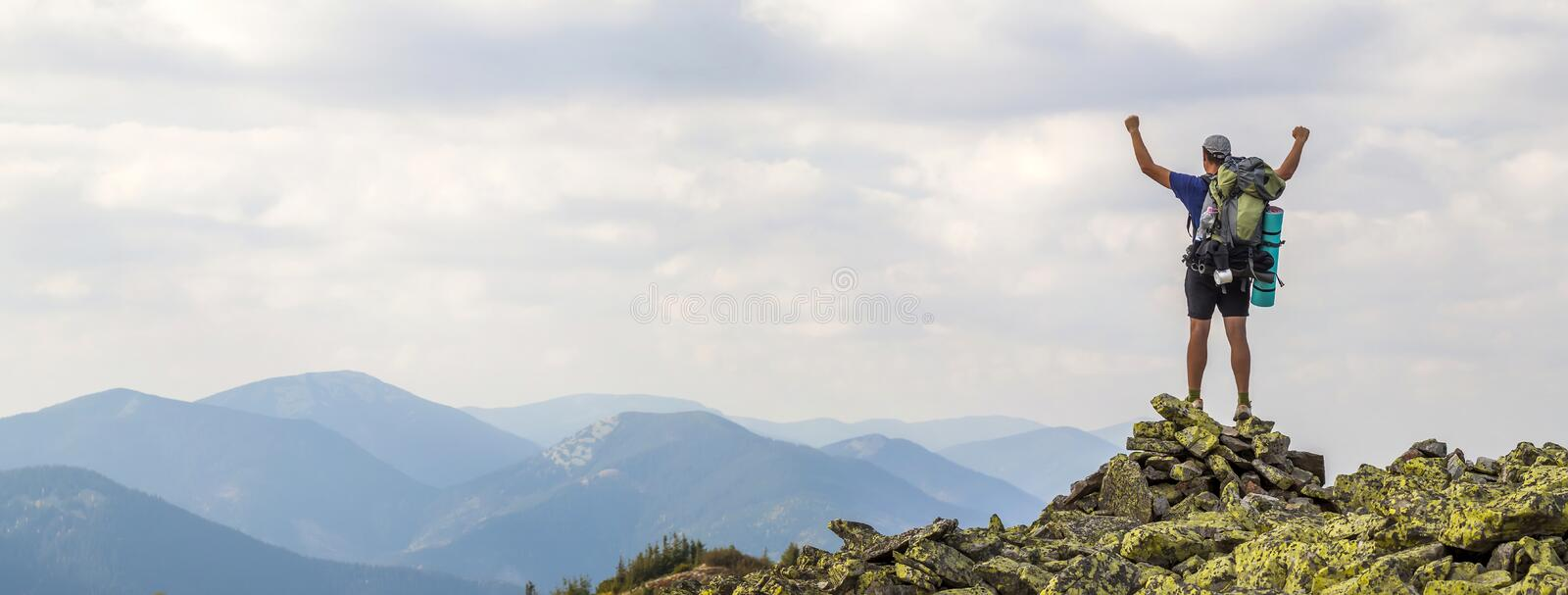 Man on peak of mountain. Emotional scene. Young man with backpack standing with raised hands on top of a mountain and enjoying mo royalty free stock photo