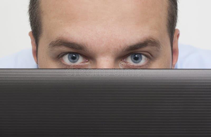 Man peeking over laptop stock image