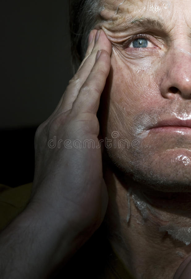 Man peeling off mask. A colour portrait photo of a forties man peeilng off a transparent mask or a chemical peel royalty free stock image