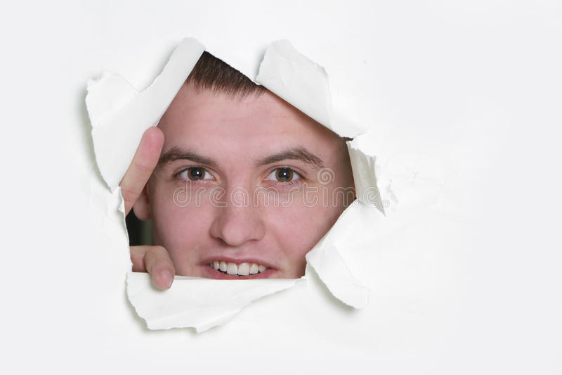 Man peeping through hole in paper royalty free stock image