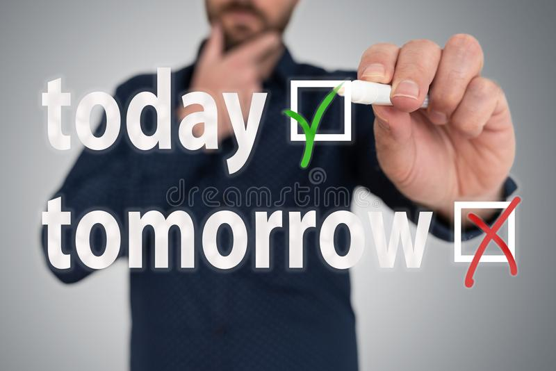 Man with pen choosing between today and tomorrow anti procrastination concept. Businessman with pen choosing between today and tomorrow anti procrastination stock image