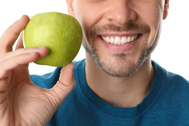 Man with perfect teeth and green apple on white background. Closeup royalty free stock photography