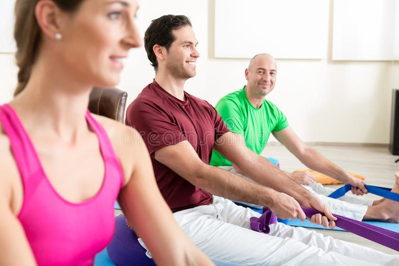 Man performing foot exercises with thera band. Smiling men with other people performing foot exercises with thera band in yoga class stock photos