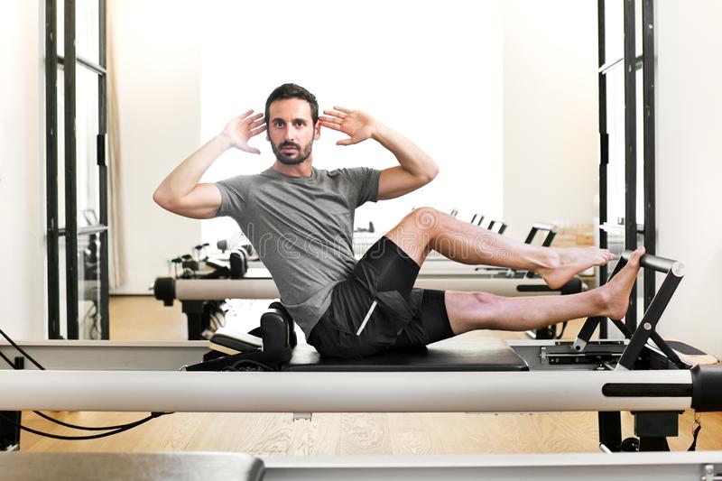 Man performing a pilates single leg stretch royalty free stock image