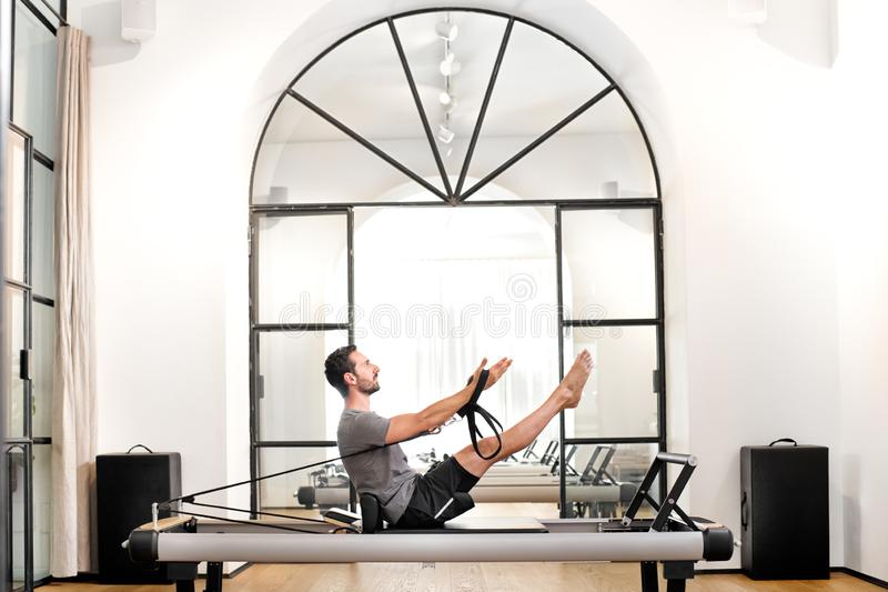 Man performing pilates teaser exercise in a gym stock photography