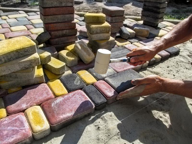 A man, performing work on laying paving slabs, knocks on bright multicolored tiles with a rubber mallet. Male hands with a rubber hammer against the background royalty free stock photo
