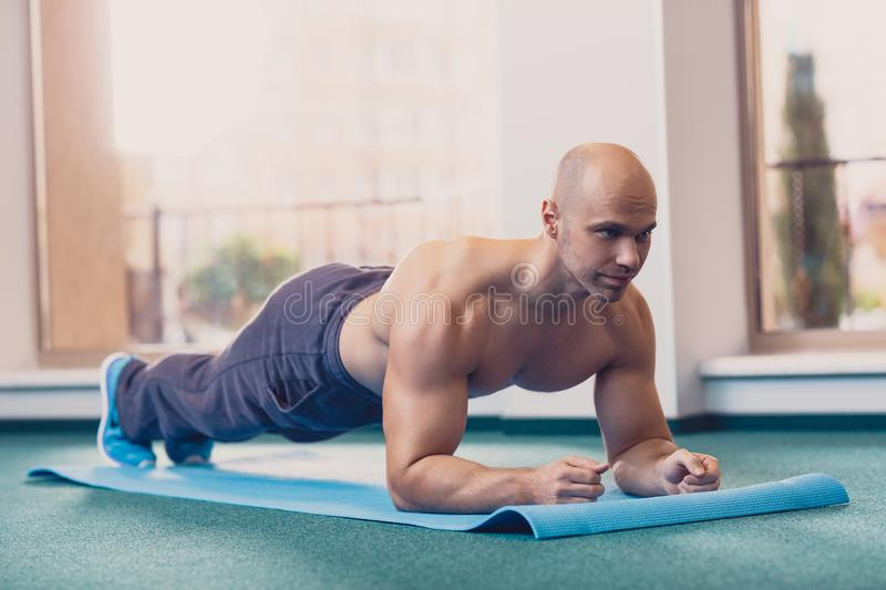 A man performs an exercise standing on his hands royalty free stock image