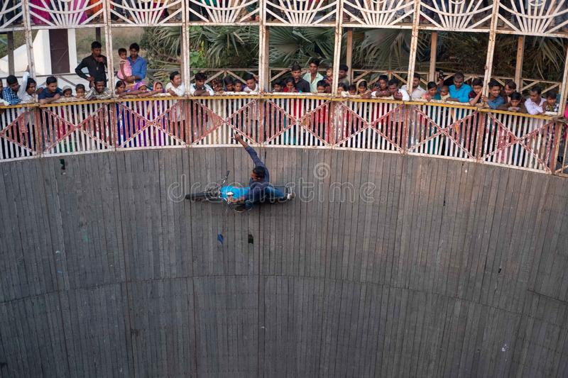 A man performs stunts while riding the wall of death at a festival surrounding NAN. Bhadarsa, Uttar Pradesh / India - April 5, 2019:A man performs stunts while stock photography