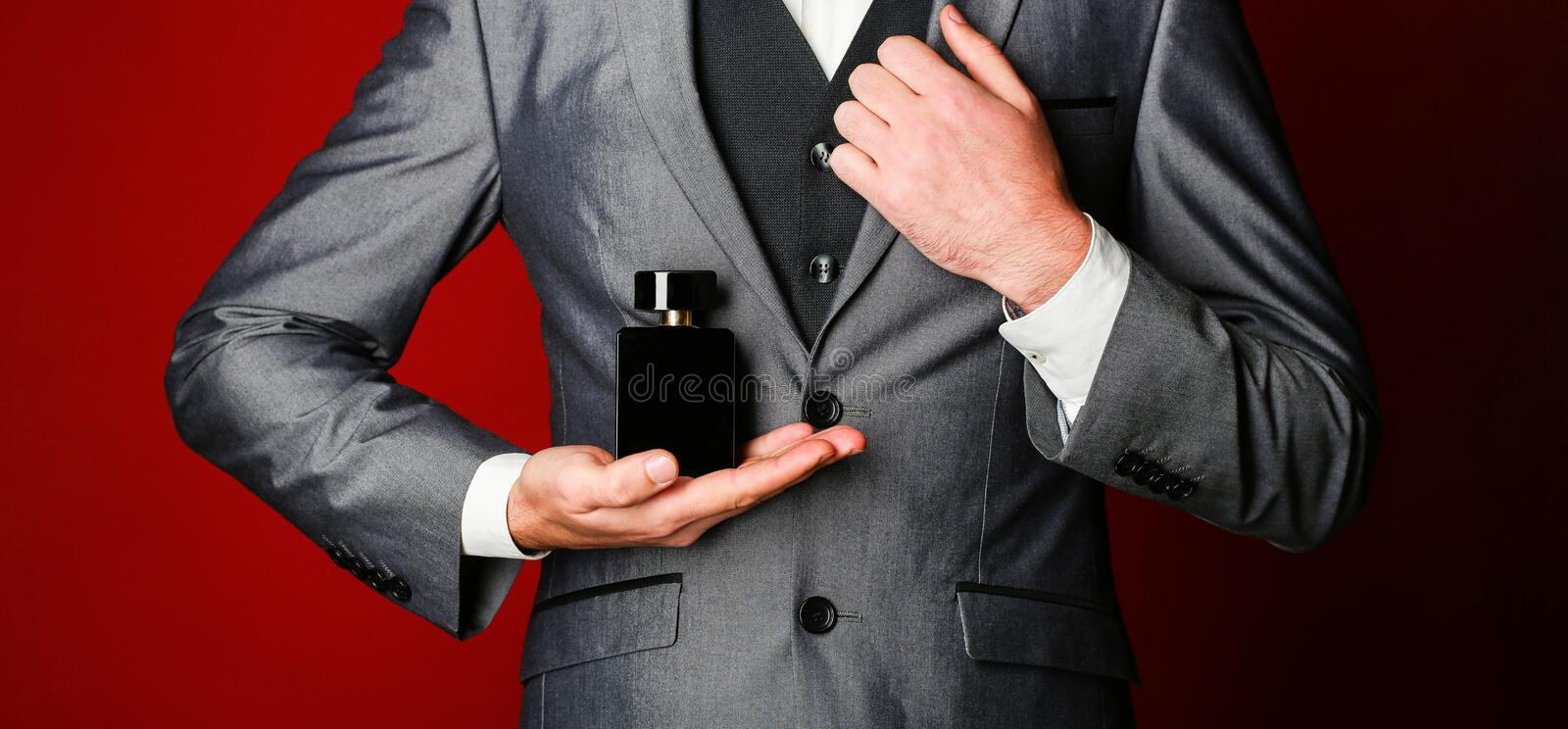 Man perfume, fragrance. Masculine perfume. Perfume or cologne bottle. Male fragrance and perfumery, cosmetics. Bearded. Man holding up bottle of perfume stock photography