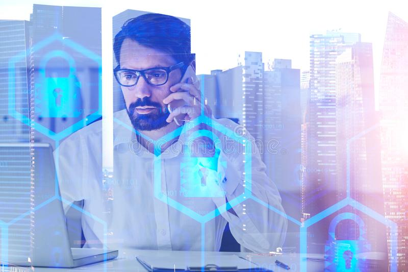 Man on phone in city, online security. Serious caucasian businessman in glasses talking on smartphone and looking at laptop over cityscape background with double stock image