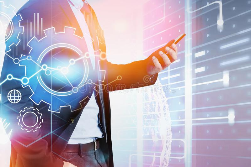 Man with phone in data center, gears. Unrecognizable man with smartphone standing in server room with double exposure of gears and internet hologram. Concept of stock image