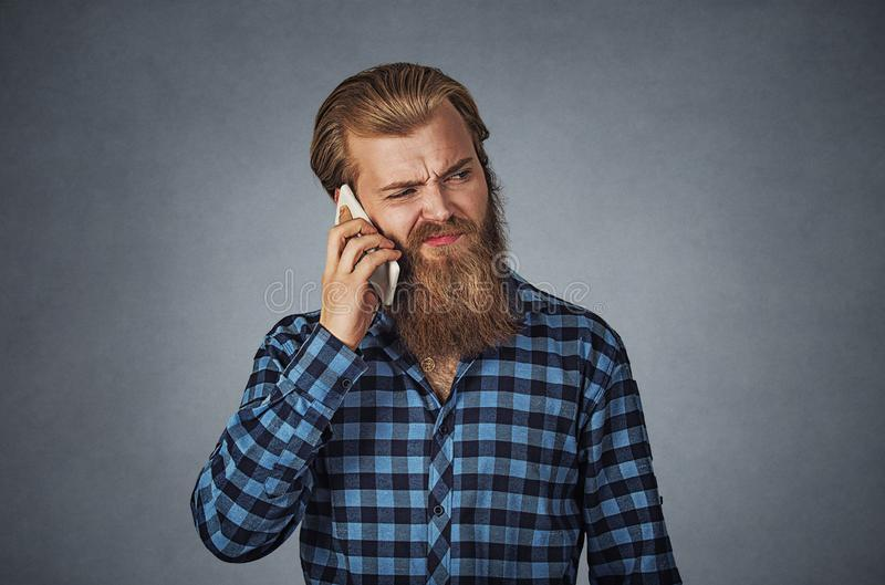 Man on the phone with headache Cellular mobile radiation concept royalty free stock photos