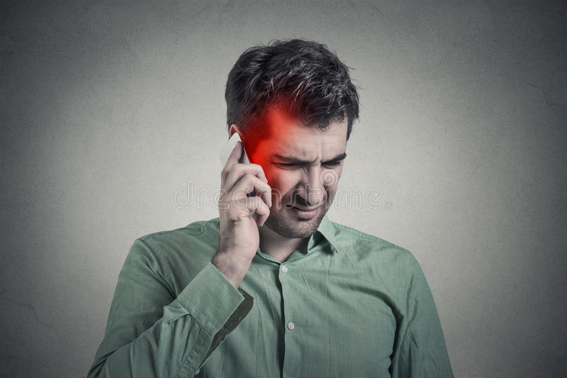 Man on the phone with headache. Cellular mobile radiation concept stock photography