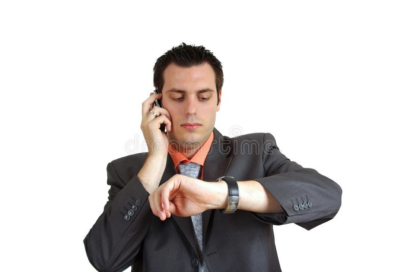 Man on the phone looking at wrist watch stock photo