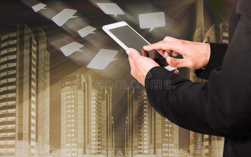 Man with phone screen on chat icons flying and cityscape background. Man touching phone screen with chat icons flying around on cityscape background stock photography