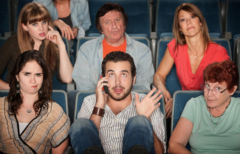 Man On Phone In Theater. Young men on phone disturbs people in theater royalty free stock photography