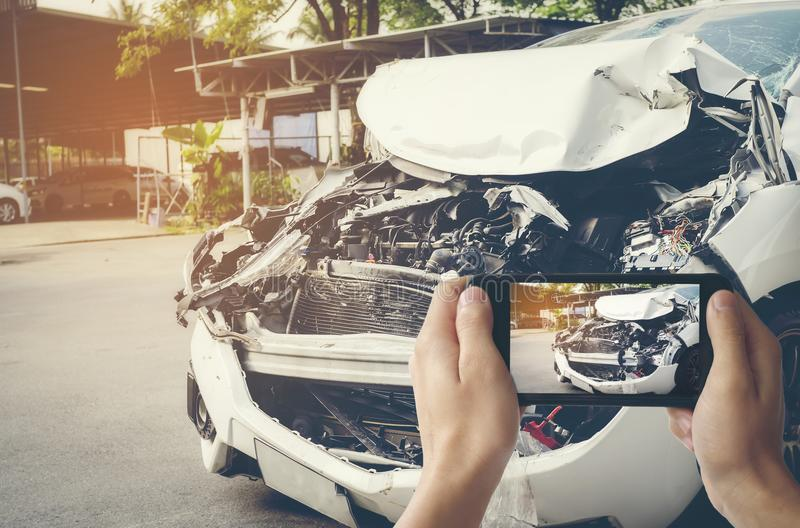 A man photographed his vehicle with accidental damage with a smart phone.Car Insurance Concept stock photography