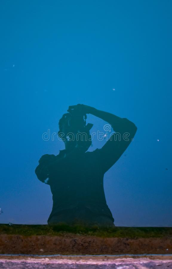 A man/photographer clicking the picture of water reflecting his body with blue sky background royalty free stock photos