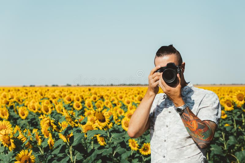 Portrait Of Male Photographer Making Photo With Camera In Hands Outdoors On Sunflowers Field. Man Photographer In Sunflower Meadow flower garden With DSLR Camera stock images