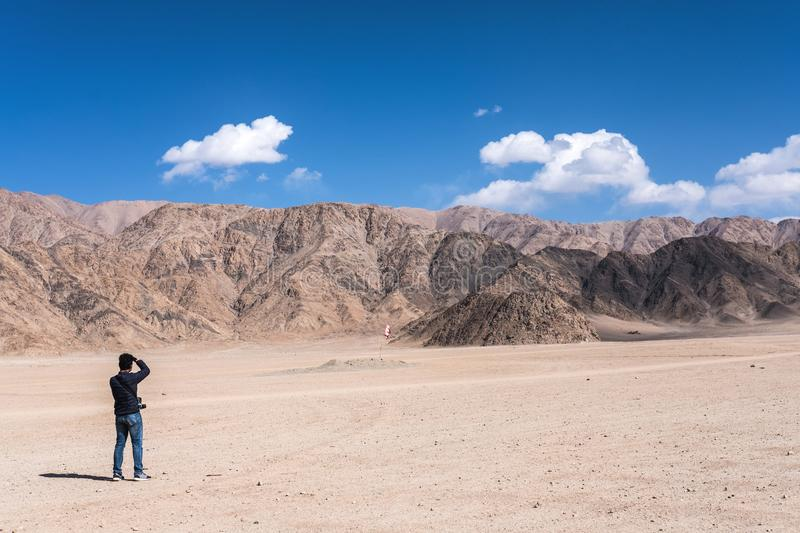 A man photographer taking a landscape photo of mountains and blue sky in Ladakh. India royalty free stock photos