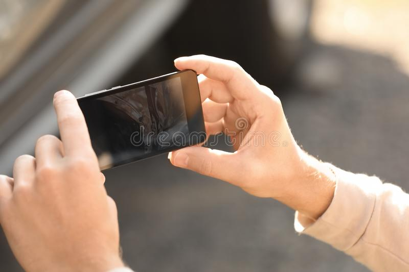 Man photographing broken car after accident for insurance claim. Closeup royalty free stock image