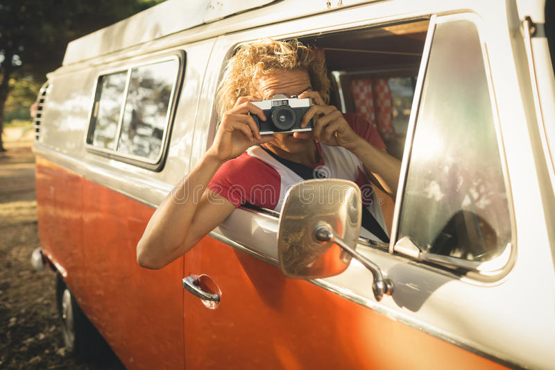 Man photographing through camera. While sitting in camper van royalty free stock image