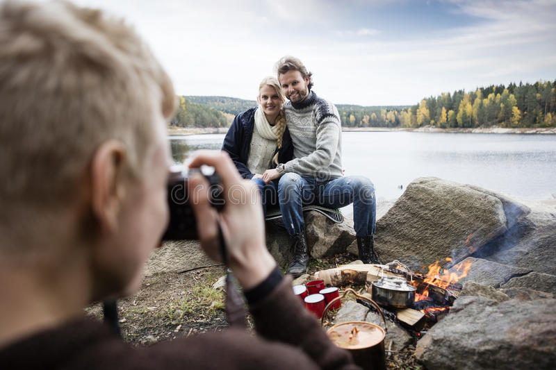 Man Photographing Couple At Lakeside Camping royalty free stock image