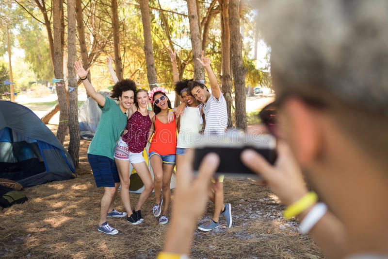 Man photographing friends at campsite. Man photographing cheerful friends while standing at campsite royalty free stock photos
