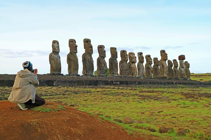 Man photographing the 15 huge Moai statues of Ahu Tongariki, Archaeological site in Easter Island, Chile, South America. Amezing landscape, adventure, amazing royalty free stock images