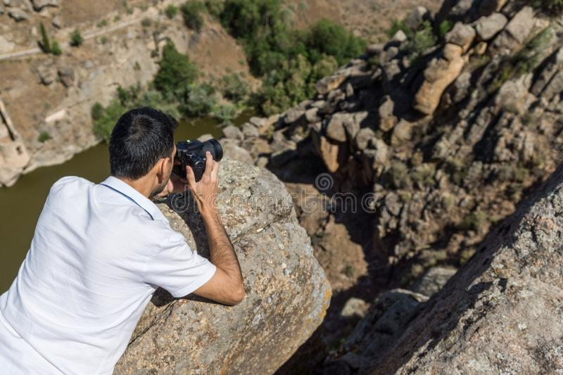 Man photographing landscape. Man in the foreground lying on a rock photographing a steep landscape beside a river royalty free stock photos