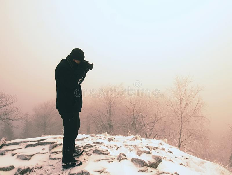Man photographing magic misty landscape in winter the mountains. stock image