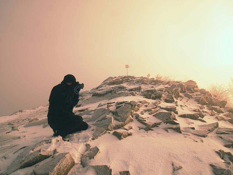 Man photographing magic misty landscape in winter the mountains. stock photography